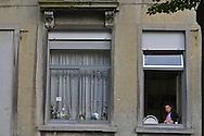 Bruxelles,17/06/2014: bambina ad una finestra, Molenbeek - girl facing out a window