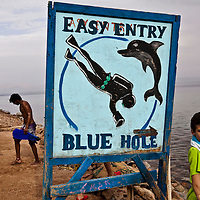 "A diver walks past a sign for the Blue Hole outside of Dahab, Egypt. The Blue Hole is notorious for the number of diving fatalities which have occurred there, earning it the sobriquet ""World's Most Dangerous Dive Site"" and the nickname ""Diver's Cemetery"". The site is signposted by a sign that says ""Blue hole: Easy entry"". Accidents are frequently caused when divers attempt to find the tunnel through the reef (known as ""The Arch"") connecting the Blue Hole and open water at about 52 m depth. According to dive experts roughly 10 people die each year. April 2012."