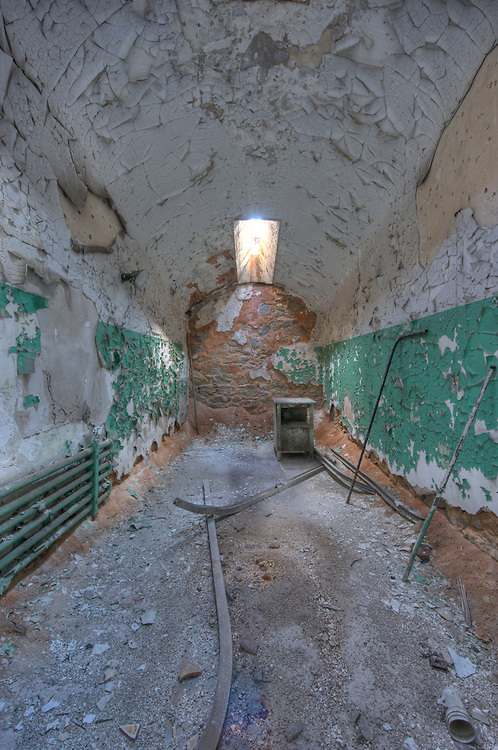 "Abandoned cell at Eastern State Penitentiary, Philadelphia, PA (US). HDR image. Opened in 1829, and dubbed the ""Pennsylvania System"" or Separate system, originated and encouraged solitary confinement as a form of rehabilitation. The prison was closed and abandoned in 1971, now operates as a museum and historic site."