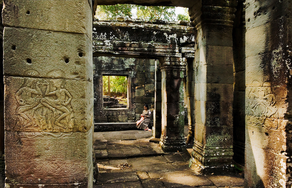 Banteay Kdei : woman guard knitting quietly and alone in a corner of the ruins; Apsara dancer reliefs on nearby pillars.  Dappled shadows cast by overhead foliage.