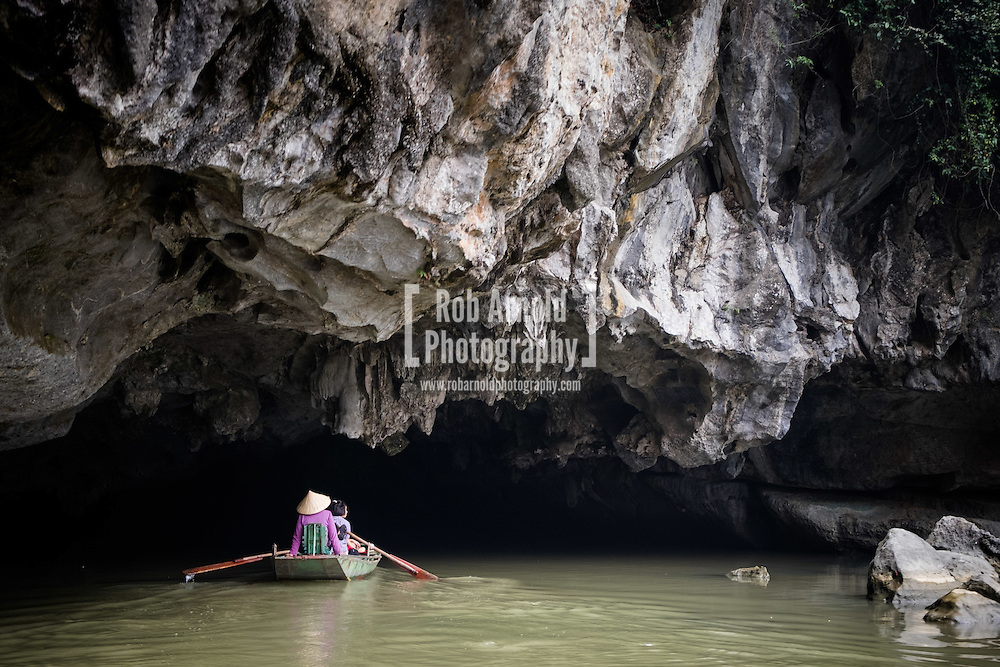 People making their way by rowing boat into a cave in Ninh Binh Province, Vietnam
