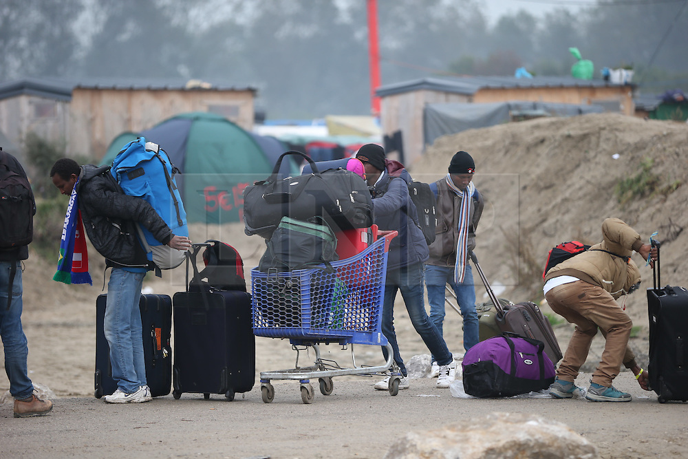 © Licensed to London News Pictures . 24/10/2016 . Calais , France . People queue to leave the Jungle migrant camp in Calais , Northern France , on the day of a planned eviction and start of the destruction of the camp . Photo credit: Joel Goodman/LNP