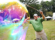 "Yellow Daisy Festival official ""Bubble Man"", Robin Booth, uses a bubble rope to make enormous bubbles for children to pop during the 2014 Yellow Daisy Festival at Stone Mountain Park on Thursday in Stone Mountain. Booth has been making the bubbles at the festival for 14 years. (Staff Photo: David Welker)"