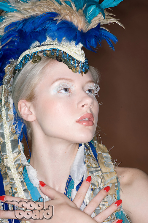 Close-up of beautiful young woman with feathered headdress