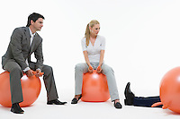 Two people sitting on space hoppers looking at fallen man against white background