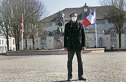 23 March 2020. Montreuil Sur Mer, Pas de Calais, France. <br /> Coronavirus - COVID-19 in Northern France.<br /> <br /> Wearing a face mask to help protect himself from coronavirus, local resident Frederic Philippe stands in the deserted main square of the ancient citadel town of Montreuil Sur Mer where a statue of Field-Marshal Sir Douglas Haig looks on. Montreuil Sur Mer was the former headquarters of the British Army during WW1. The usually bustling market square is now deserted since From March 16th French lawmakers imposed strict controls on the movement of people in an effort to stem the spread of the virus. Anyone leaving their home must carry with them an 'attestation,' in a effect a self administered permit to allow them out of the house. If stopped by the police, one must produce a valid permit along with identification papers. Failure to do so is punishable with heavy fines. Movement in France has been heavily restricted by the government.<br /> <br /> Montreuil Sur Mer was the headquarters of the British Army under Field-Marshal Sir Douglas Haig from March 1916 to April 1919. Over 1,200 year old, the ancient fortified  town with its high ramparts has endured through history, surviving the plague and King Henry VIII's invasion of France in 1544 when the Duke of Norfolk under Henry VIII's command laid a disastrous siege to the town which held firm until Norfolk was forced to withdraw in 1545. Residents are confident the ancient town can survive the coronavirus too. <br /> Photo©; Charlie Varley/varleypix.com