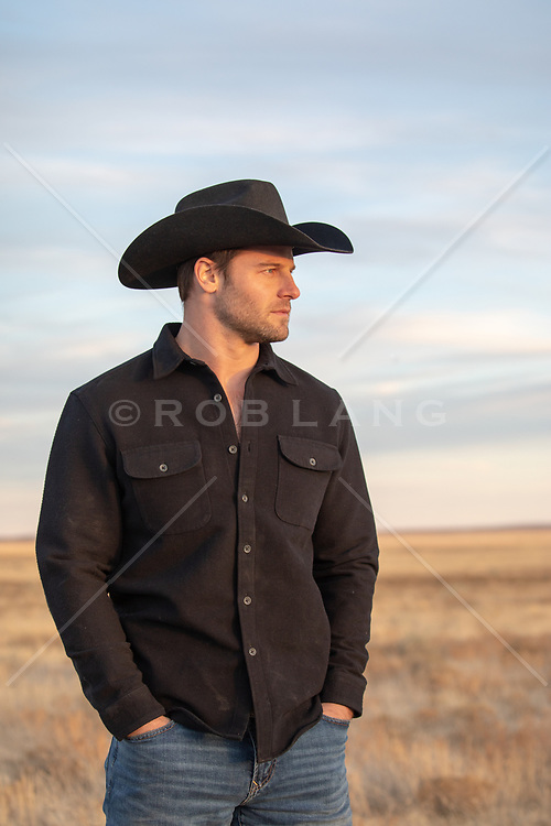 cowboy with hands in pockets looking at an open field at sunset