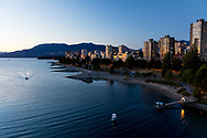 The view of the skyline and mountains from the Burrard Street Bridge looking out towards Stanley Park, English Bay and sunset beach at dusk.  Vancouver, British Columbia, Canada
