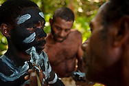 Man having make up applied to his face for the snake dance. he snake dance is a traditional dance which takes place on special occations for the inhabitabts of Rah Lava Island. These days it is often performed for the visiting tourists. Rah Lava Island, Torba Province, Vanuatu