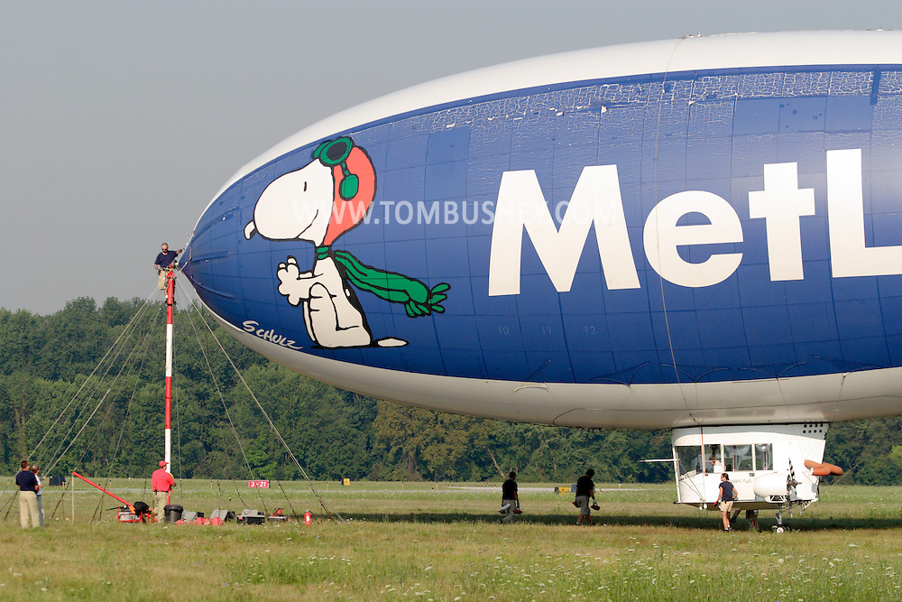 Montgomery, NY - Members of the ground crew, including one man on the mooring mast, prepare the Met Life blimp Snoopy Two for take off from Orange County Airport  on July 26, 2008.