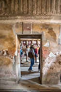 View of female tourist through doorway as tourists explore the Men's Baths at Pompeii, layers of time shown through wall texture, paint, decoration.