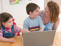 Mother and Children at Table With Laptop