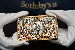 "© Licensed to London News Pictures. 01/06/2018. LONDON, UK. A Sotheby's technician presents ""An Imperial Presentation Fabergé jewelled gold and enamel box"", 1897, by Michael Perchin (Est. GBP150-200k) at a preview of the Russian Pictures and Russian Works of Art, Fabergé & Icons sale which will take place at Sotheby's, New Bond Street on 5 June.  Photo credit: Stephen Chung/LNP"