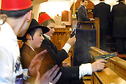 Young Orthodox Jewish boy shoot cap guns and bang on drums every time Haman is mentioned in the congregation during the Megillah reading for Purim in Walford road synagogue. Purim is one of the most entertaining Jewish holidays.  It commemorates the time when the Jewish people living in Persia were saved from extermination from a massacre by Haman. Due to the courage of a young Jewish woman called Esther, it is customary for men dress u and to hold carnival-like celebrations.