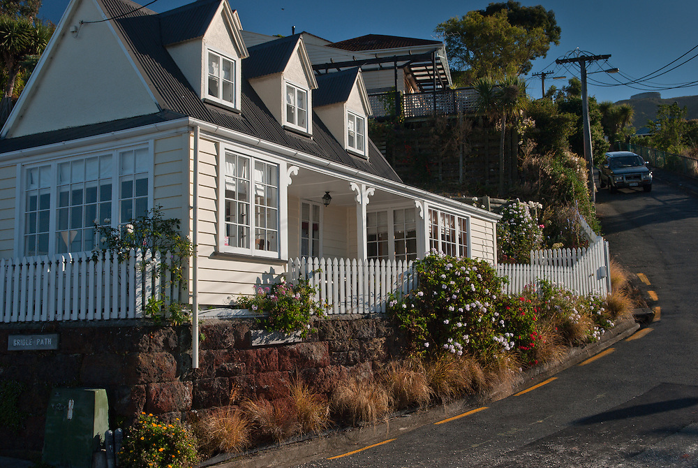 Morning sunlight on a traditional New Zealand cottage with three dormer windows and white picket fence at the end of the Bridle Path, Lyttelton