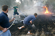 """Neighbors battle a brush fire with garden hoses after a Sept. 3 wind storm downed a power line into the field in the bench neighborhood. Craig Burden, who owns the house next to the charred field, came home from McCall a few days later to find a large hole burned into his trampoline and his garden hose missing..""""At least they saved the house from going up,"""" he said."""