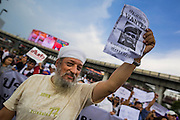 "25 MAY 2014 - BANGKOK, THAILAND: A Thai-Indian carries a ""wanted"" poster with a picture of Gen. Prayuth Chan-ocha, leader of the coup that unseated the elected civilian government. Public opposition to the military coup in Thailand grew Sunday with thousands of protestors gathering at locations throughout Bangkok to call for a return of civilian rule and end to the military junta.     PHOTO BY JACK KURTZ"