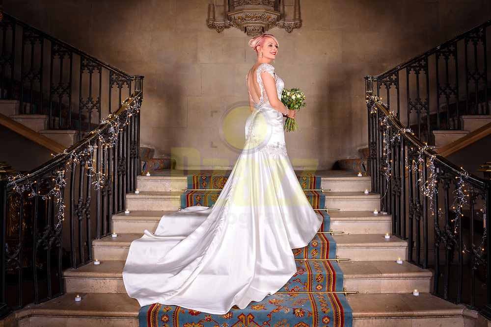 Beautiful shot of the bride in her wedding dress on the magnificent sweeping staircase at Ashridge House