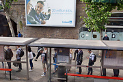 Beneath a billboard ad for online jobs website LinkedIn a queue of bus passengers wait for the next service at Waterloo Station during the morning rush-hour, on 5th June 2019, in London, England.