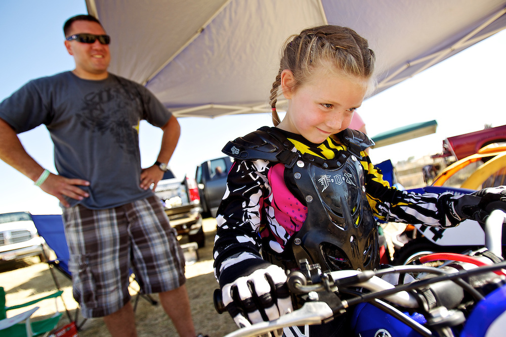Payton Sterling, 5, takes her spot atop her 50cc motorcycle before her father, Josh Sterling, leads her out to the track for warm-up laps Wednesday. Sterling competed in her first race without training wheels at the North Idaho Fair during the Wednesday evening races.