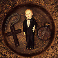 Small model of 1940s butler or waiter lying with small Bakelite crucifix and tarnished pocket watch in brown bowl with intricate pattern