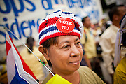 """22 JUNE 2011 - BANGKOK, THAILAND: A PAD supporter wears a vote """"no"""" button at a rally in Bangkok on Wednesday, June 22. The PAD (People's Alliance for Democracy) or Yellow Shirts, as they are popularly called, has called for a """"No"""" vote in Thailand's national election, scheduled for July 3. PAD leadership hopes the no vote will negate the vote of Yingluck Shinawatra, leader of the Pheua Thai party. Yingluck is the youngest sister of exiled former Prime Minister Thaksin Shinawatra, deposed by a military coup in 2006. Yingluck is currently leading in opinion polls, running well ahead of incumbent Prime Minister Abhisit Vejjajiva, head of the Democrat party, which in one form or another has ruled Thailand for most of the last 60 years.     Photo by Jack Kurtz"""