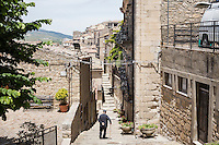 GANGI, ITALY - 30 MAY 2015: An elderly man walks in the historical center of Gangi, Italy, on May 30th 2015. Gangi is a town with a population of 7,000 between Palermo and Catania, in the centre of Sicily, whose local administration is giving away abandoned houses of the historical centre for free. The Mayor of Gangi Giuseppe Ferrarello conceived the initiative of giving houses for free as a means to diversify the local economy - primarily dependent on agriculture and animal husbandry - by boosting tourism-related activities, and consequently counteract the phenomenon of depopulation that is typical of many small Italian towns where employment possibilities have been on a downward trajectory for years. The renovations of the assigned homes have also given work to local artisans.