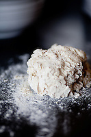 A ball of pizza dough on a dark counter dusted with flour.