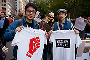 "Two men hold T-shirts printed on site, one with a graphic red clenched fist titled ""99%"", the other ""Occupy wall street""."