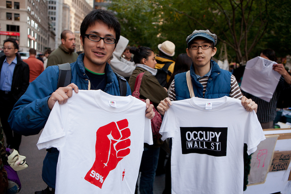 """Two men hold T-shirts printed on site, one with a graphic red clenched fist titled """"99%"""", the other """"Occupy wall street""""."""