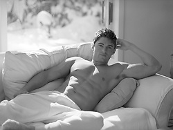 sexy man without a shirt reclining on a couch at home