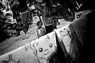 Mirelis Zapata, 4, accompanies her mother, Nilda Zapata, 33, as she hangs laundry to dry on a clothes line in a Warao community in downtown Ciudad Guayana in northeastern Venezuela.  In an effort to escape poverty, hunger and to be closer to health care facilities, approximately 300 Warao indigenous persons from the Delta Amacuro have settled in Ciudad Guayana.