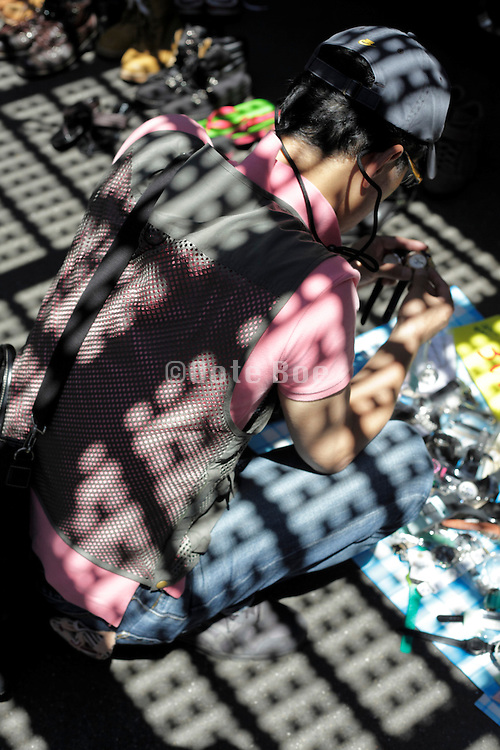 person looking for things at a flea market with grating shadow projection