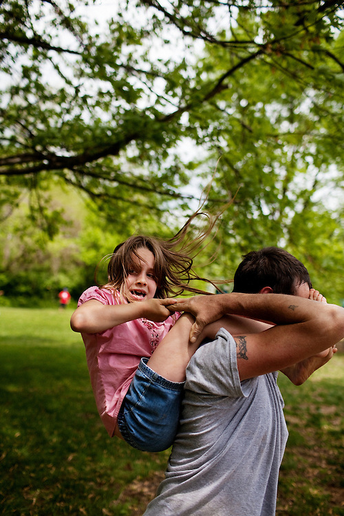Jessie Sellers Sr. tips his daughter Lacey off his back while playing with her in Athens, Ohio. Lacey and her identical twin sister Kacey were both born deaf and live in the impoverished town of Chauncey, Ohio.