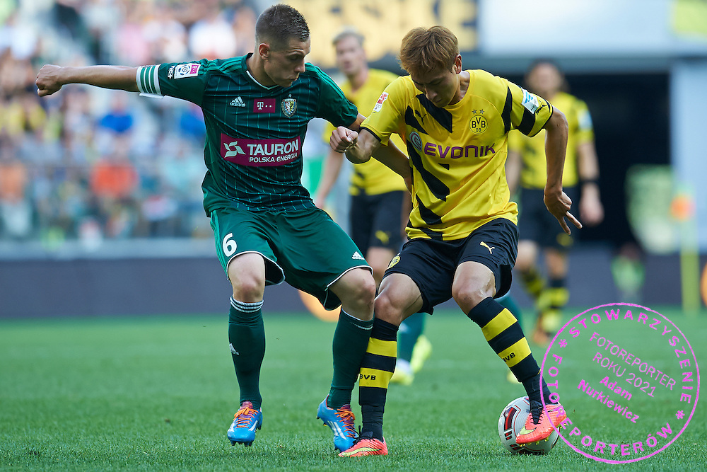 (R) Dong-Won Ji of Dorussia Dortmund fights for the ball with (L) Tomasz Holota of Slask Wroclaw during international friendly soccer match between WKS Slask Wroclaw and BVB Borussia Dortmund on Municipal Stadium in Wroclaw, Poland.<br /> <br /> Poland, Wroclaw, August 6, 2014<br /> <br /> Picture also available in RAW (NEF) or TIFF format on special request.<br /> <br /> For editorial use only. Any commercial or promotional use requires permission.<br /> <br /> Mandatory credit:<br /> Photo by &copy; Adam Nurkiewicz / Mediasport