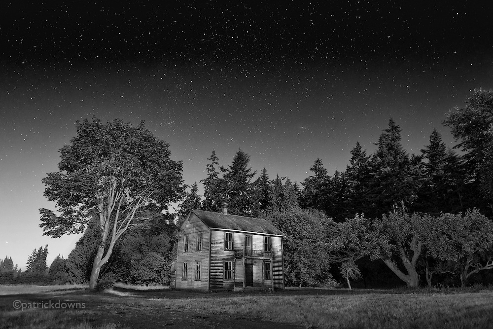 A 100+ year old farmhouse, bought from the Sears Catalog in the early 1900s, sits under the stars and lit by a full moon. Near Sequim WA and the Dungeness River.