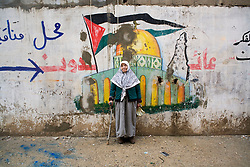 "A woman who survived the 1948 forced exodus from Palestine (""Nakba"" in Arabic) and again the exodus from Nahr al-Bared in 2007 when fighting broke out between the Lebanese army and extremists, stands in front of a mural depicting Jerusalem's Dome of the Rock after returning to Nahr al-Bared in 2008."