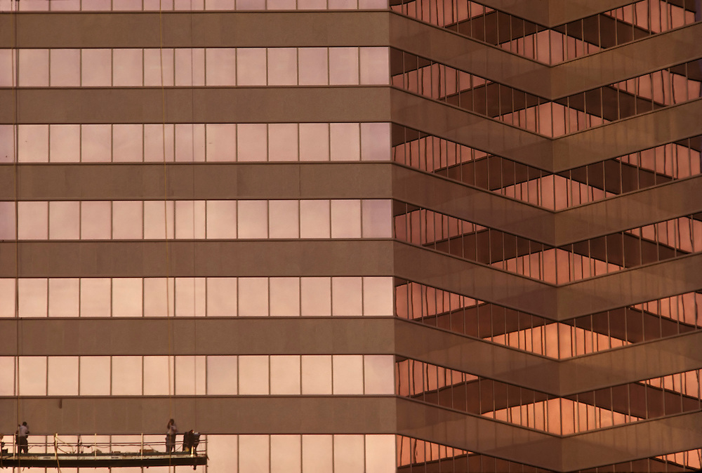 Window washers on side of Houston, Texas, Galleria area offfice building with the color of sunset reflected by its glass.
