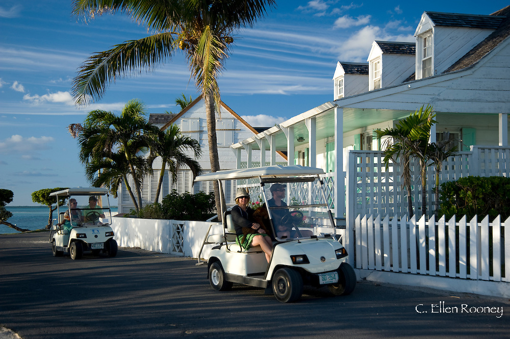 Tourists riding around Dunmore Town in golf carts.  Harbour Island, Eleuthera,<br /> The Bahamas