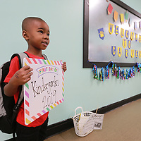 Keilan Patten, 5, gets his photo taken on his first of school at Carver Elementary School