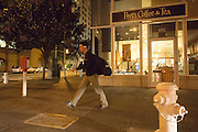 Een man loopt 's avonds door San Francisco langs een koffietentje.<br />