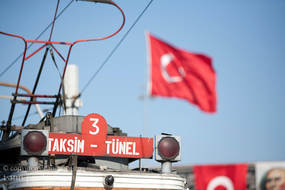The historic tram which serves ?stiklal Avenue set in front of Turkish flags prepared for Victory Day in August