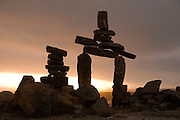 "Inukshuk (stone marker) above the town of Iqaluit, Nunavut, Canada. Iqaluit, with population of 6,000, is the largest community in Nunavut as well as the capital city. It is located in the southeast part of Baffin Island. Formerly known as Frobisher Bay, it is at the mouth of the bay of that name, overlooking Koojesse Inlet. ""Iqaluit"" means 'place of many fish'. The image is part of a collection of images and documentation for Hungry Planet 2, a continuation of work done after publication of the book project Hungry Planet: What the World Eats, by Peter Menzel & Faith D'Aluisio."