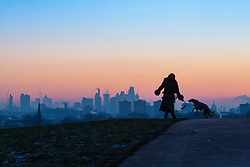 London, December 12 2017. A dog walker with her whippet is in silhouette against the skyline before the sun rises on a clear very cold morning in London, seen from Primrose Hill in Camden. © Paul Davey