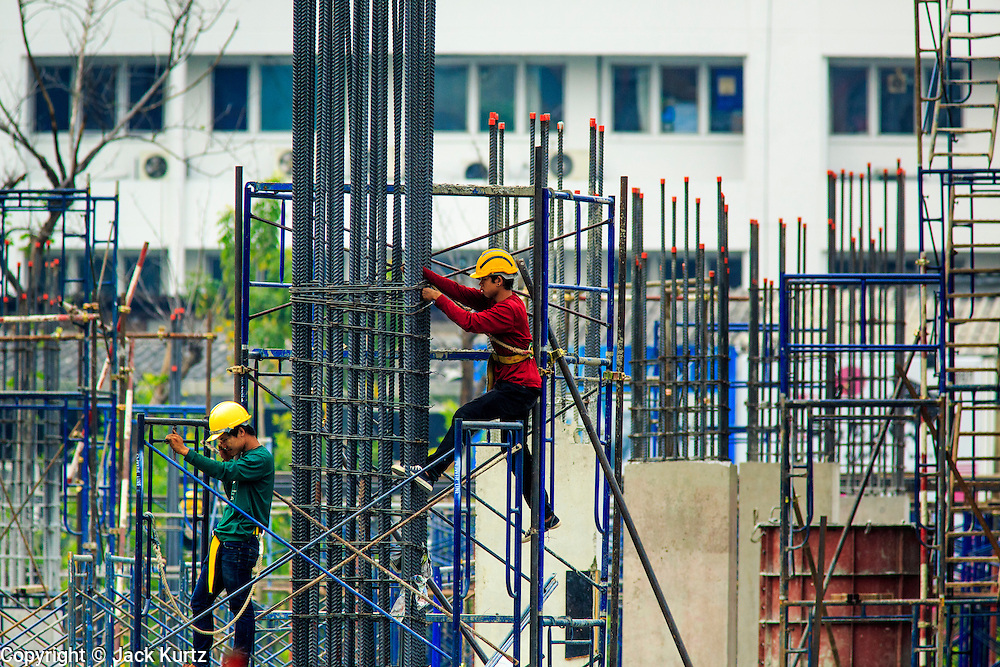 22 FEBRUARY 2013 - BANGKOK, THAILAND: Workers on the scaffolding in the Siam Square 1 construction site. Siam Square 1 is a new retail development under construction on Th. Rama I between Henri Durant and Phaya Thai across the street from Siam Center. It will join a very crowded retail environment in the Ratchaprasong Intersection area that includes Siam Center, Siam Paragon, Gaysorn, Erawan and MBK.     PHOTO BY JACK KURTZ