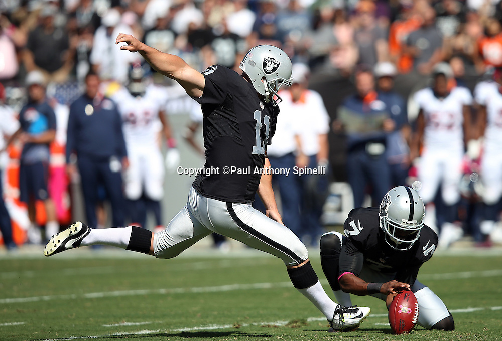 Oakland Raiders punter Marquette King (7) holds as Oakland Raiders kicker Sebastian Janikowski (11) attempts a first quarter field goal that gets blocked by the Denver Broncos during the 2015 NFL week 5 regular season football game against the Denver Broncos on Sunday, Oct. 11, 2015 in Oakland, Calif. The Broncos won the game 16-10. (©Paul Anthony Spinelli)