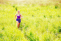 Young woman jogging on path through tall grass, portrait