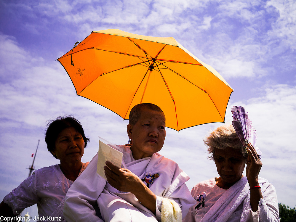 02 FEBRUARY 2013 - PHNOM PENH, CAMBODIA: Cambodian women mourning late King Norodom Sihanouk take shade on the plaza in front of the Royal Palace during the mourning period for Sihanouk, who ruled Cambodia from independence in 1953 until he was overthrown by a military coup in 1970. Sihanouk died in Beijing, China, in October 2012.      PHOTO BY JACK KURTZ