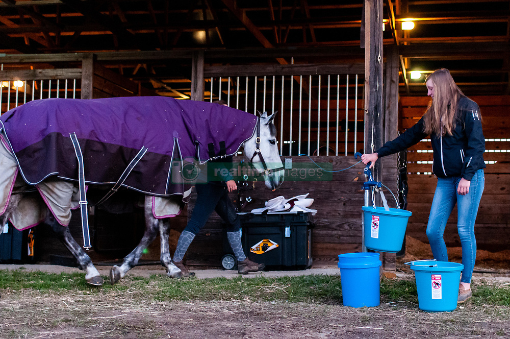 March 22, 2019 - Raeford, North Carolina, US - March 23, 2019 - Raeford, N.C., USA - CLAIRE TISCKOS fills water buckets as the day gets started at the sixth annual Cloud 11-Gavilan North LLC Carolina International CCI and Horse Trial, at Carolina Horse Park. The Carolina International CCI and Horse Trial is one of North AmericaÃ•s premier eventing competitions for national and international eventing combinations, hosting International competition at the CCI2*-S through CCI4*-S levels and National levels of Training through Advanced. (Credit Image: © Timothy L. Hale/ZUMA Wire)