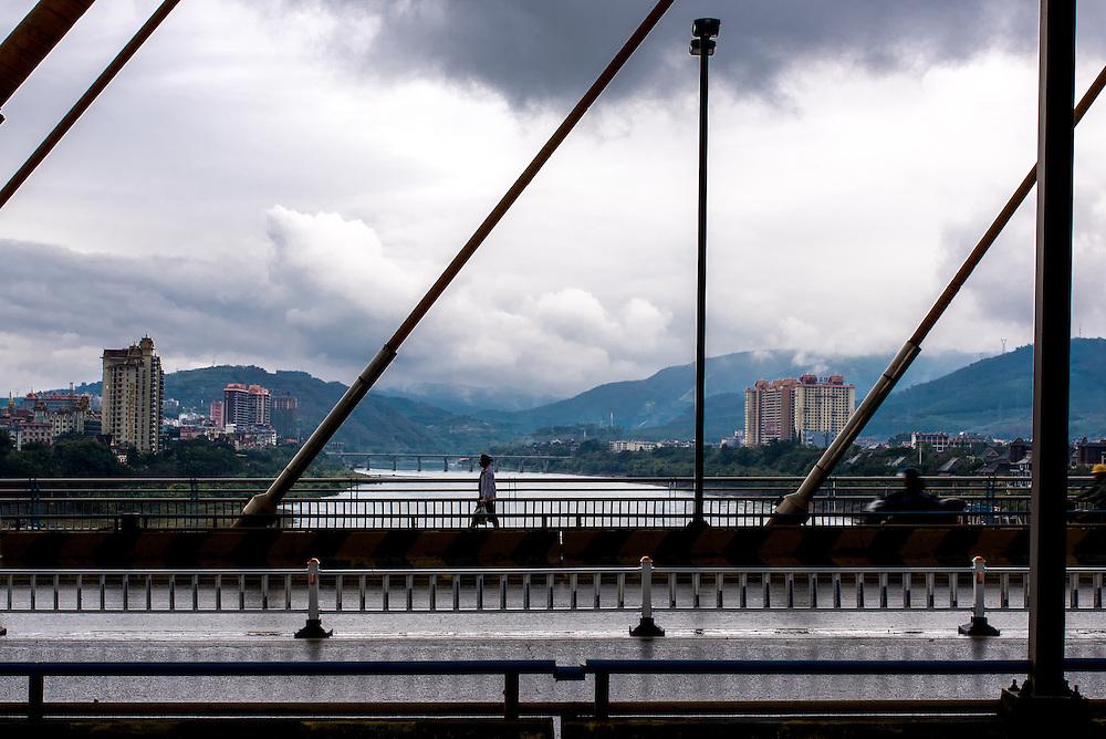A woman crosses a bridge spanning the Lancang (Mekong) in Xishuangbanna, Yunan, China.